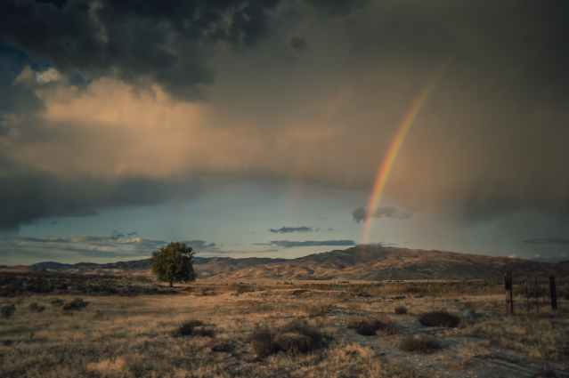 photo of rainbow under clouded sky
